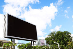 Billboard with empty screen, against blue cloudy sky Stock Photos