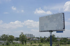 Billboard with empty screen, against blue cloudy sky Stock Image