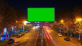 A billboard with green chroma key on a background of a city night landscape of fast moving cars with long exposure.The. A billboard with green chroma key on a stock video