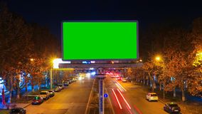 A billboard with green chroma key on a background of a city night landscape of fast moving cars with long exposure.The. A billboard with green chroma key on a stock video footage