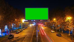 A billboard with green chroma key on a background of a city night landscape of fast moving cars with long exposure. 4K. Time Lapse video stock video footage