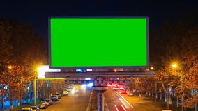 A billboard with green chroma key on a background of a city night landscape of fast moving cars with long exposure. Time. Lapse video stock video