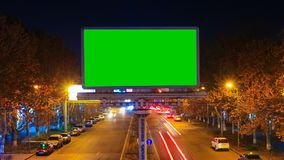 A billboard with green chroma key on a background of a city night landscape of fast moving cars with long exposure. Time. Lapse video. The camera is approaching stock footage