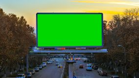 A billboard with green chroma key on the background of fast moving cars at sunset.  stock video