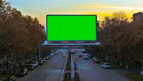 A billboard with green chroma key on the background of fast moving cars at sunset. The camera moves away. A billboard with green chroma key on the background of stock video