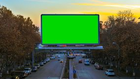 A billboard with green chroma key on the background of fast moving cars at sunset. Time Lapse video. The camera is. Approaching stock video footage