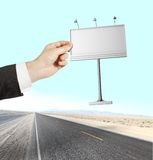 Billboard. Hand holding Billboard on a road background royalty free stock image