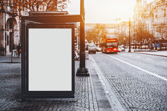 Billboard mock-up on city bus stop in Portugal. White empty information mock-up on city bus stop, blank vertical billboard near paved road with red touristic bus royalty free stock photo