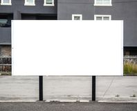 Billboard poster on roadside with blank white mock up area. Isolated template with concrete buildings at background. Urban street environment stock images