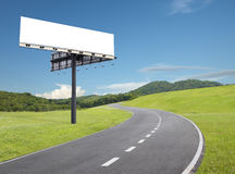Billboard by the road. Blank billboard beside an empty curve road royalty free stock image
