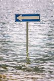 Billboard road arrow to the left partially submerged by flood water. A road sign lies in the middle of a lake of water royalty free stock photos