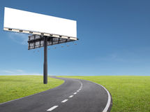 Billboard by the roadside. Blank billboard at roadside of a curve road royalty free stock images