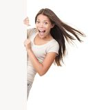 Billboard sign woman ecstatic. Billboard sign. Funny ecstatic young woman screaming joyful while showing copy space on blank white billboard sign. Beautiful Royalty Free Stock Images