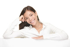 Billboard sign woman smiling friendly. Woman showing billboard sign smiling friendly. Young beautiful woman standing behind blank white billboard. Casual young stock images