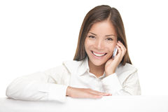 Billboard sign woman talking on mobile phone. Woman showing billboard sign while talking on mobile phone and smiling. Young beautiful woman standing behind blank stock images