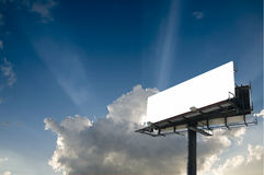Billboard and Sky. Blank double back to back billboard with sun beam bursts in a partly cloudy sky Stock Photo