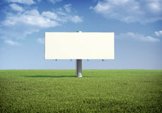 Billboard standing in a field of grass. Ad billboard standing in a field of grass Royalty Free Stock Image