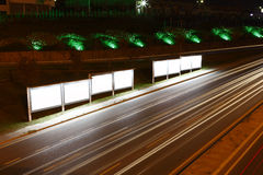 Billboards roadside, night. Billboards illuminated on side of road with light trails at night Royalty Free Stock Images