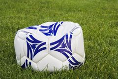 Bille de football à plat blanche et bleue sur l'herbe Photo libre de droits