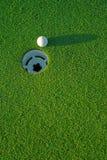 Bille de golf en fonction à côté du trou 4 Photographie stock libre de droits