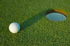 Bille de golf en fonction à côté du trou 1 Images stock
