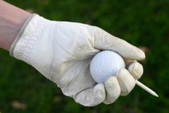 Bille de golf enfilée de gants de fixation de main avec le té image libre de droits