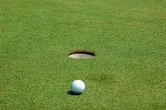 Bille de golf près de trou Photographie stock