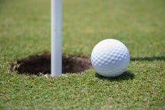 Bille de golf près de trou images stock