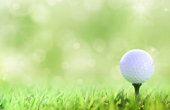 Bille de golf sur le té au-dessus d'un vert photographie stock libre de droits