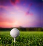 Bille de golf sur le té au coucher du soleil Images stock