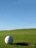Bille de terrain de golf près de trou Photographie stock libre de droits