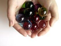 Billes colorées de bain dans des mains Images libres de droits