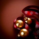 Billes d'or de Noël avec la bande rouge de cadeau photographie stock