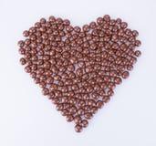Billes de chocolat les boules de chocolat dans l'amour forment sur un fond Photographie stock libre de droits