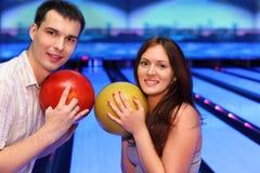 Billes de prise d'homme et de femme dans le bowling Images stock