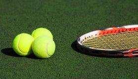 Billes de tennis et une raquette Images stock