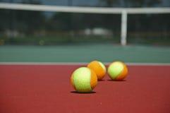 Billes de tennis multicolores sur la cour dure Photo libre de droits