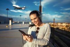 Billet d'avion de commande de jeune femme par le comprimé Photos stock