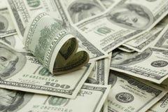 Billet d'un dollar 100 en forme de coeur sur la pile de l'argent Image stock