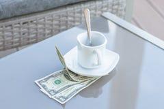 Billet d'un dollar américains et tasse de café vide sur une table en verre de café extérieur Paiement, astuce image stock