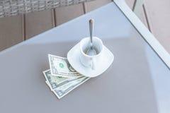 Billet d'un dollar américains et tasse de café vide sur une table en verre de café extérieur Paiement, astuce photos stock
