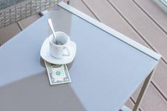 Billet d'un dollar américains et tasse de café vide sur une table en verre de café extérieur Paiement, astuce photographie stock libre de droits