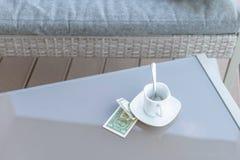 Billet d'un dollar américains et tasse de café vide sur une table en verre de café extérieur Paiement, astuce photo stock