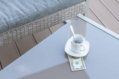 Billet d'un dollar américains et tasse de café vide sur une table en verre de café extérieur Paiement, astuce photographie stock