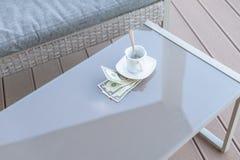 Billet d'un dollar américains et tasse de café vide sur une table en verre de café extérieur Paiement, astuce images stock