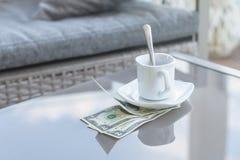 Billet d'un dollar américains et tasse de café vide sur une table en verre de café extérieur Paiement, astuce image libre de droits