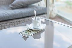 Billet d'un dollar américains et tasse de café vide sur une table en verre de café extérieur Paiement, astuce photo libre de droits