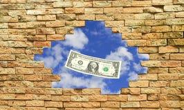 Billet d'un dollar en trou latéral de mur de bloc de brique image libre de droits