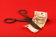 Billet de banque de coupe de ciseaux euro au-dessus de fond rouge Image stock