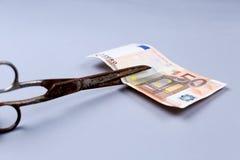 Billet de banque d'euros et ciseaux Photo stock
